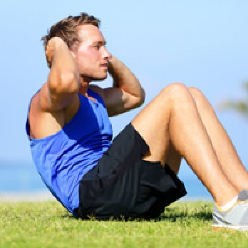 Sit-ups – fitness man training sit up outside in grass in summer